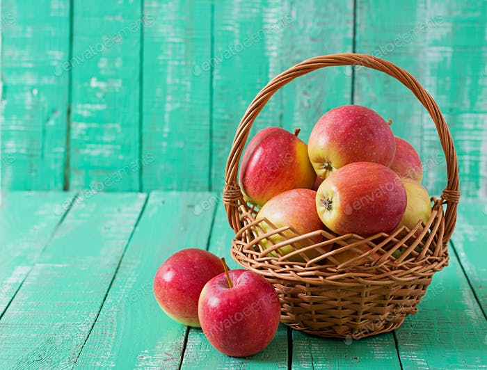 Ripe red apples in a basket on a bright wooden background