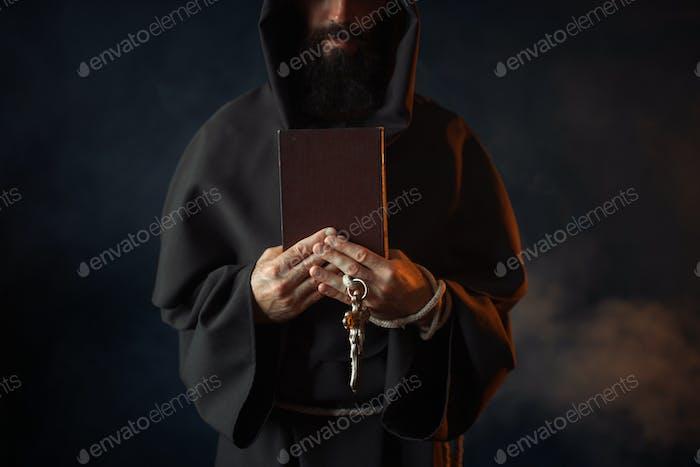 Mittelalterlicher Mönch hält Buch und Holzkreuz in den Händen