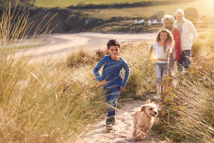 Grandchildren And Pet Dog Exploring Sand Dunes With Grandparents On Winter Beach Vacation