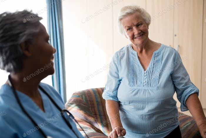 Smiling nurse and senior woman looking at each other