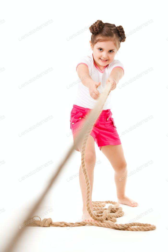 Small positive girl in stylish clothing standing, playing in pulling rope and smiling over white