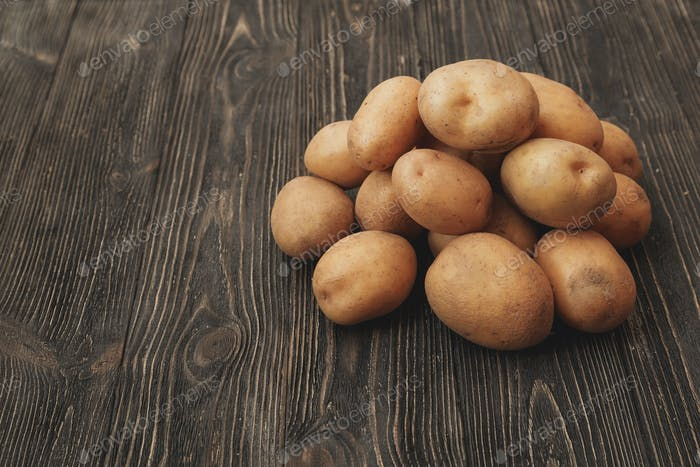 Handful of Raw harvested potatoes on dark wooden background.