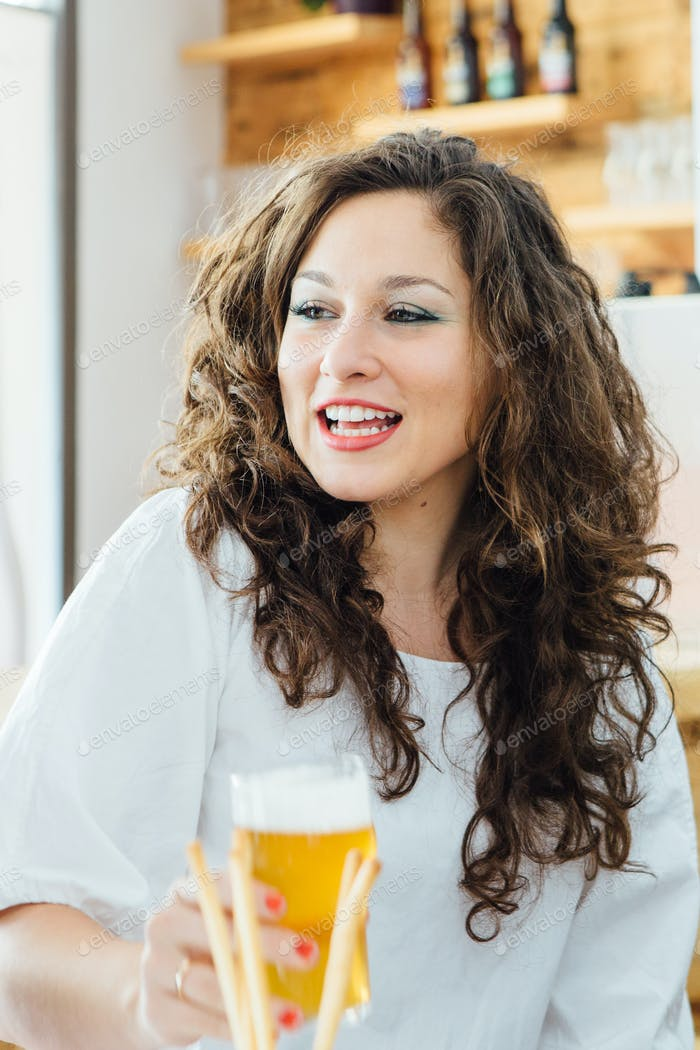 Portrait of smiling woman with beer