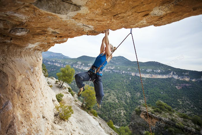 Woman climber struggling to make next movement up