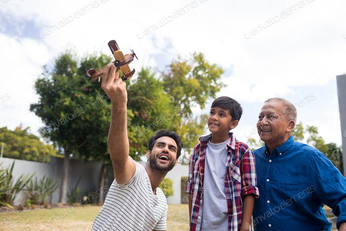 Boy with grandfather looking at man holding toy airplane