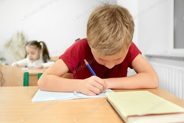 Schoolboy sitting at desk, writing with pen in copybook