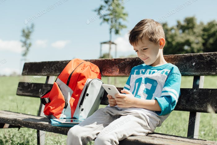 Schoolboy taking a break on a bench and playing with a mobile
