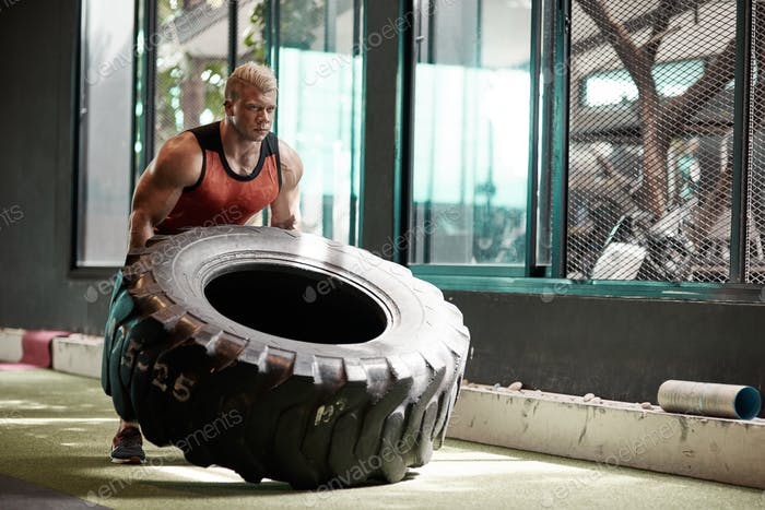 Powerful strongman flipping the tire