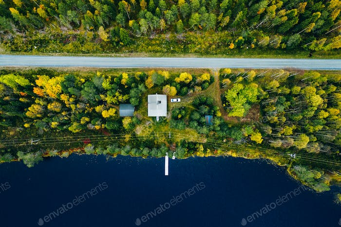 Aerial top view of log cabin or cottage with road in spring forest by the lake in Finland
