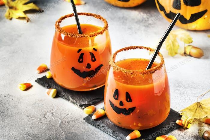 Halloween orange festive drink and pumpkin guards on gray autumn background