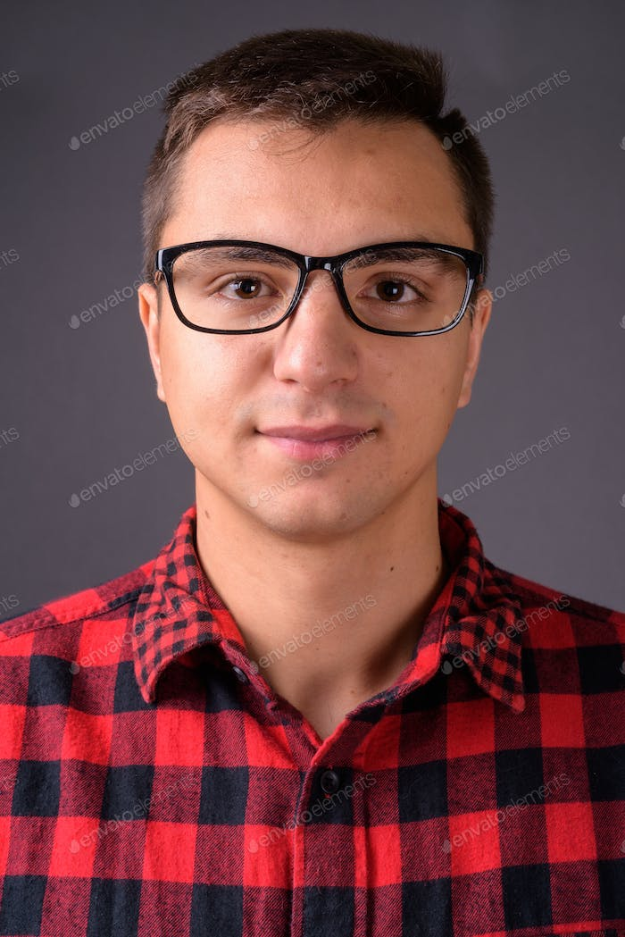Studio shot of young handsome man against gray background