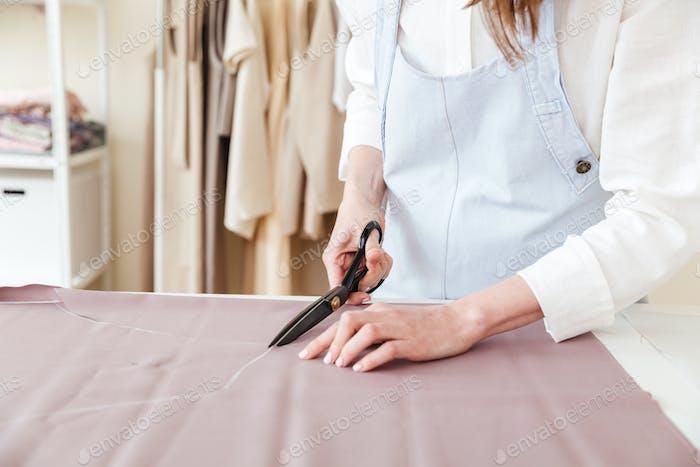 Frau mit einer Schere, um Stoff zu schneiden