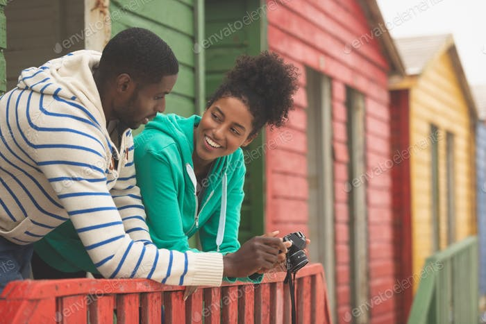Side view of happy young Multi-ethnic couple using digital camera while standing at beach hut