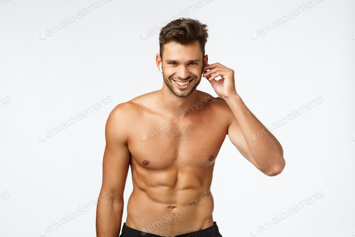 Workout, earphones and music concept. Attractive shirtless athlete with naked torso, put wireless