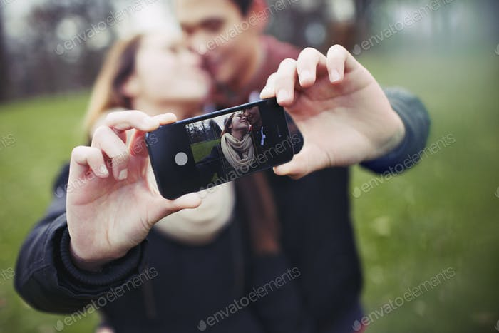 Romantic teenage couple taking self portrait with cell phone