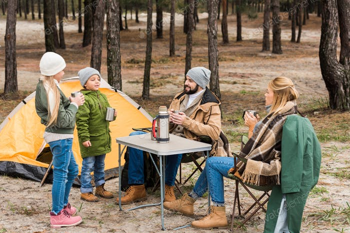 happy young family on camping in forest drinking hot tea