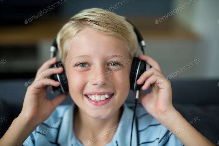 Smiling boy listening to music on headphones in living room