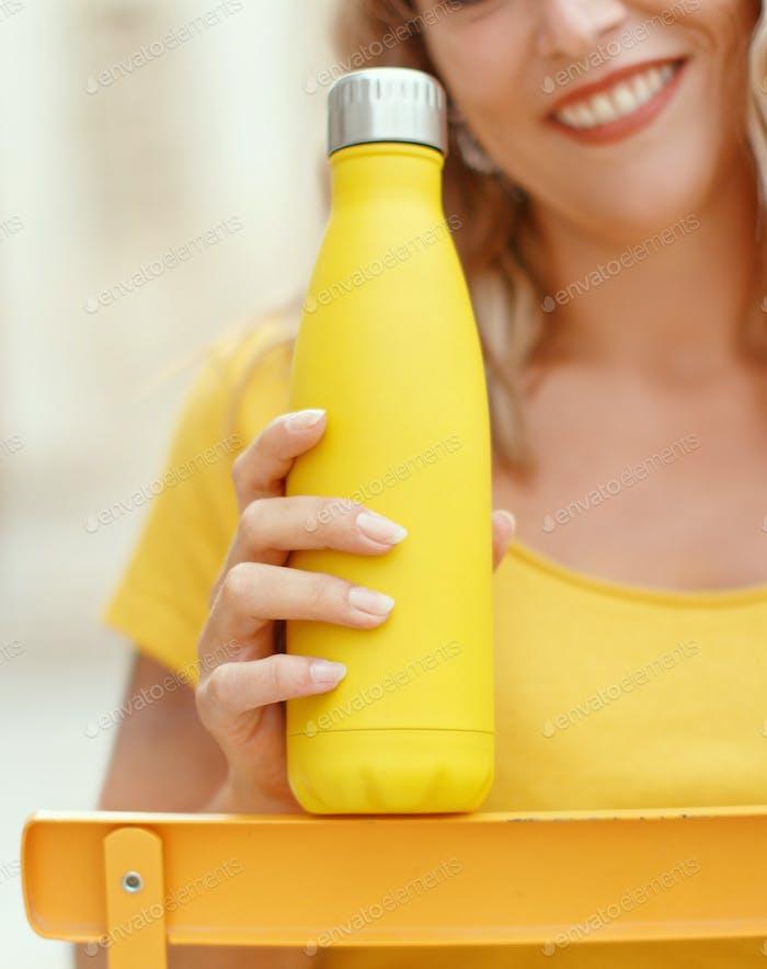 Junge Frau hält gelbe wiederverwendbare Flasche