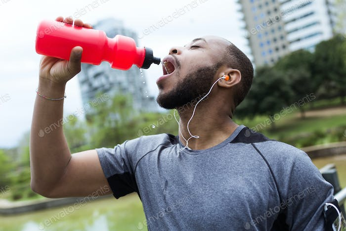 Fit and sporty young man drinking water in the city.