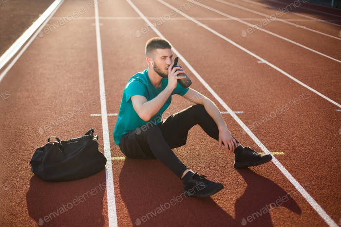 Young guy in sportswear thoughtfully drinking water sitting on running track at stadium