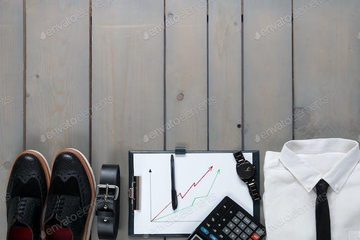 Geschäftsmann, Arbeitsoutfit auf grauem Holzhintergrund.
