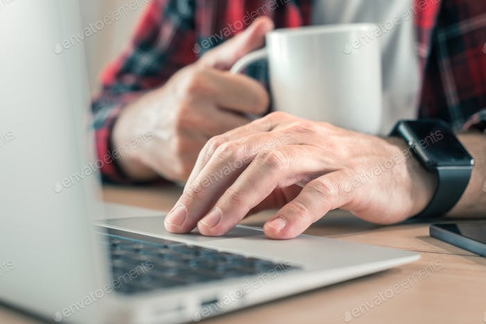 Freelancer using laptop computer and drinking coffee in home office