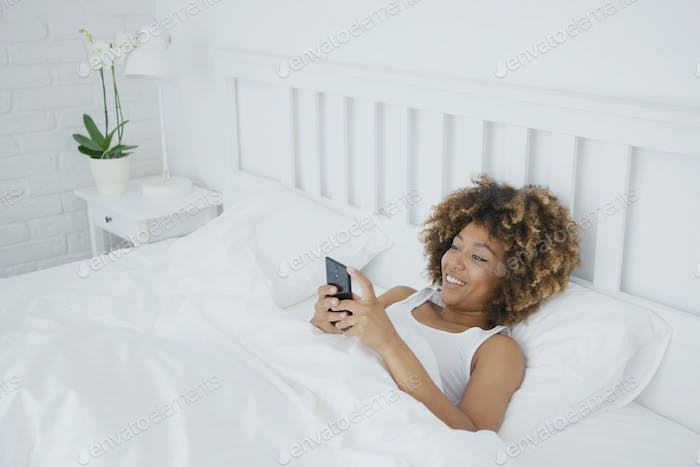 Smiling woman relaxing with phone in bed