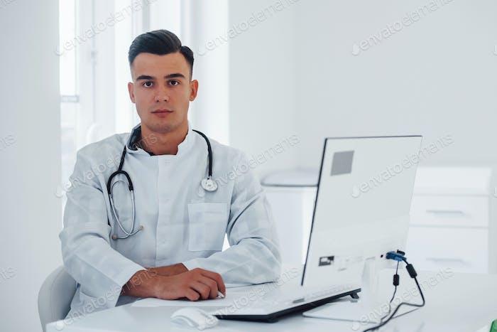 Junge stilvolle männliche Arzt mit Stethoskop ist tagsüber in der Klinik