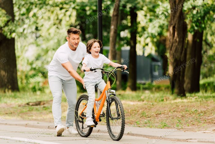 full length view of father pushing bike while son ridding on bicycle
