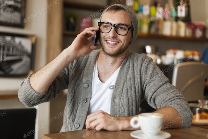 Hipster man talking by mobile phone at cafe