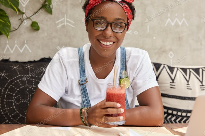 Image of cheerful hipster wears transparent glasses, dressed in casual outfit, drinks fresh cocktail