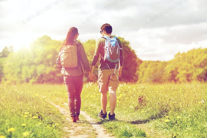 happy couple with backpacks hiking outdoors