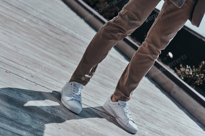 Fashion starts with shoes.  Close-up of modern man in white shoes standing outdoors
