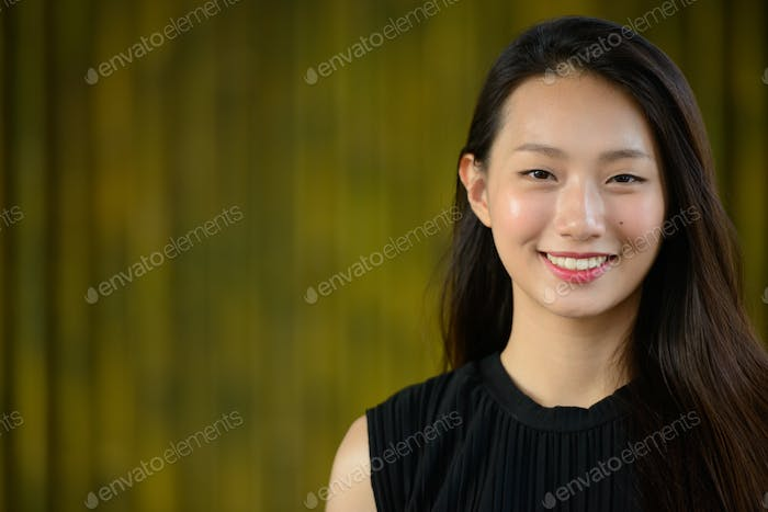 Happy young beautiful Asian businesswoman against bamboo fence