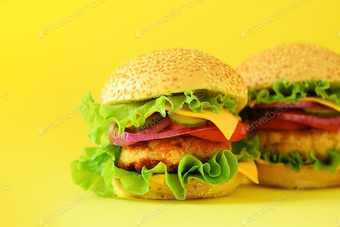 Fast food - juicy hamburgers on yellow background. Take away meal. Unhealthy diet concept with copy
