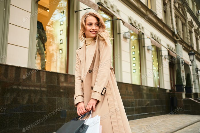 Smiling stylish blond girl in beige coat with shopping bags joyfully looking away on city street