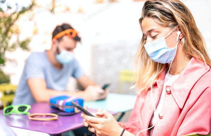Junge Frau mit Kopfhörern mit Tracking-App auf dem Mobiltelefon