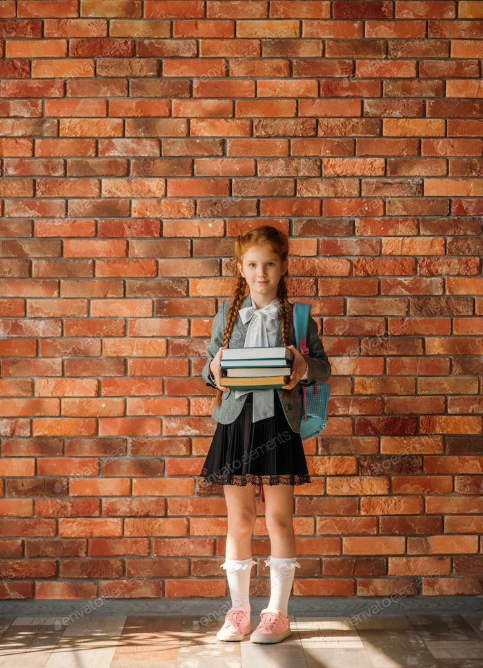 Schoolgirl with schoolbag holds stack of textbooks