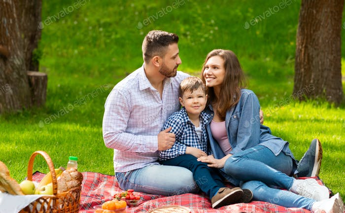 Loving family with cute child spending weekend together on picnic at park