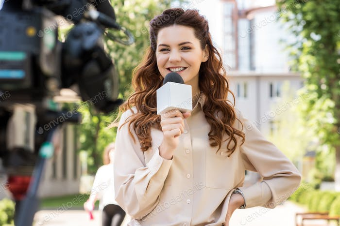 attractive smiling female journalist with microphone talking to digital video camera