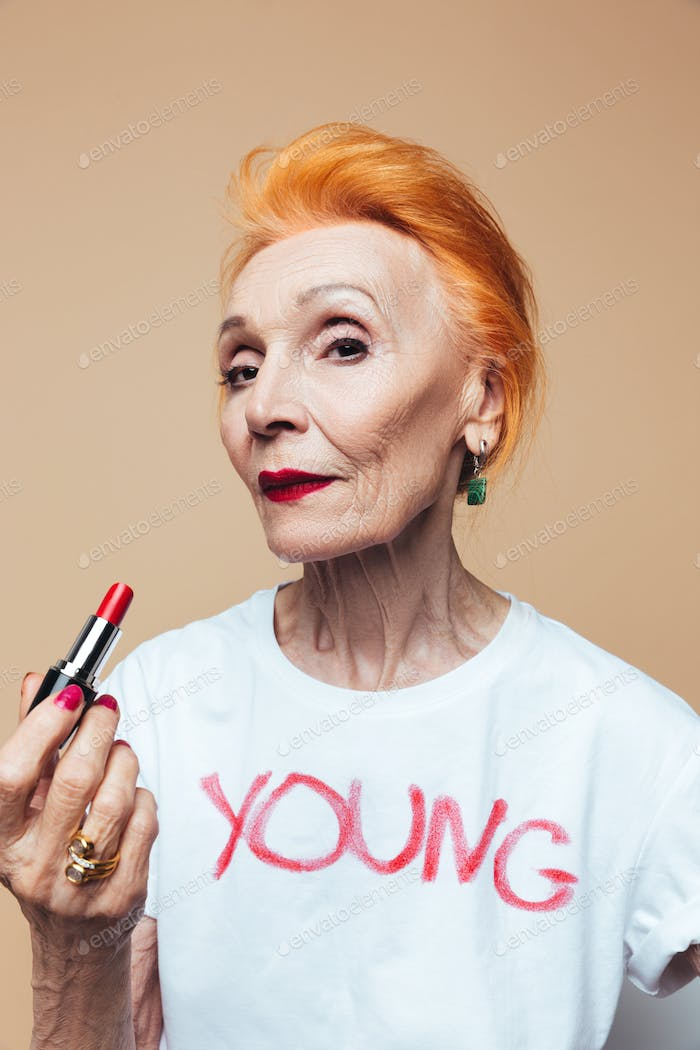 Mature redhead fashion woman holding red lipstick