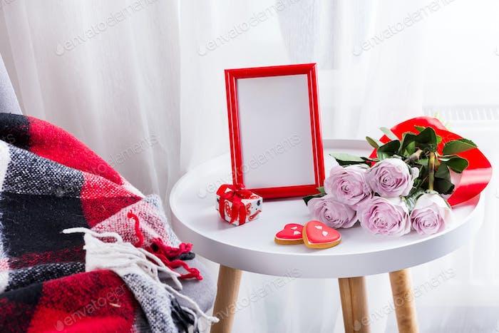 Hausgemachte Valentinstag Herz Cookies, rosa Rosen und roten Rahmen auf weißen Tisch mit Stuhl und rot