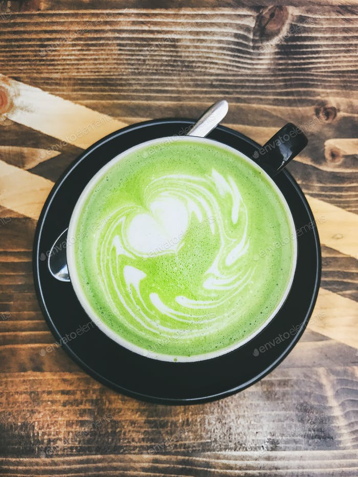 Tasse Matcha Latte in schwarzer Tasse auf Holzuntergrund