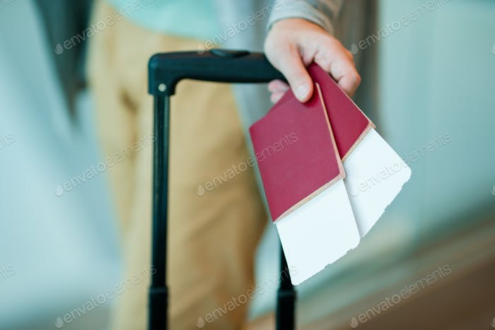 Nahaufnahme von Pässen mit Bordkarte und Gepäck in männlichen Händen am Flughafen