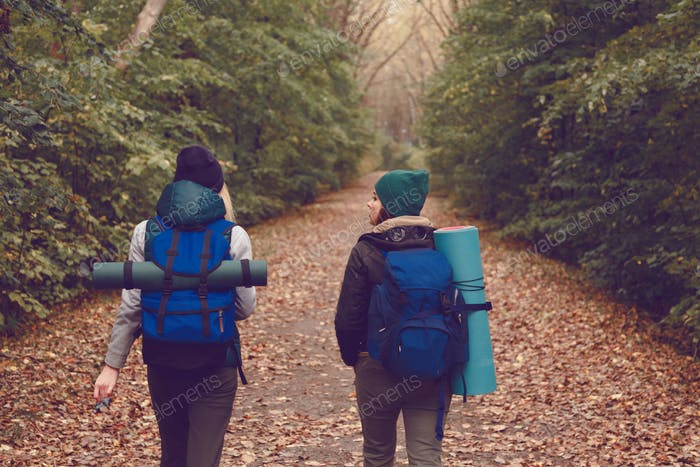 Girlfriend traveler with backpacks went hiking in the woods.
