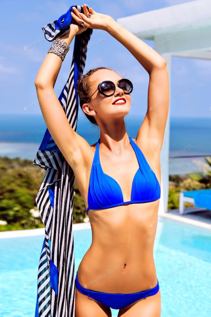 Young sexy brunette woman in bikini posing at luxury hotel