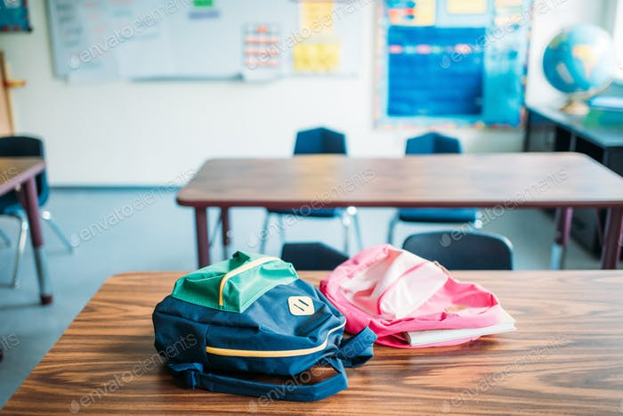 backpacks laying on desk in school classroom