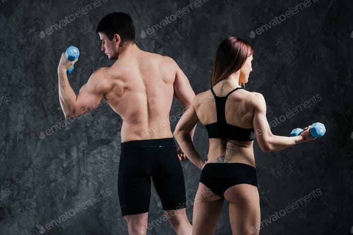 An attractive fitness couple of sporty male holds barbell and slim blond female holds dumbbells over