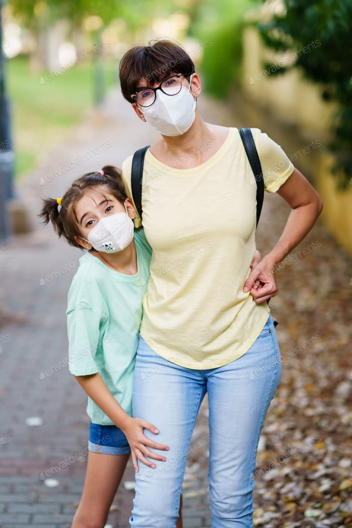 Placeit - Middle-aged mother and daughter standing on the street wearing masks