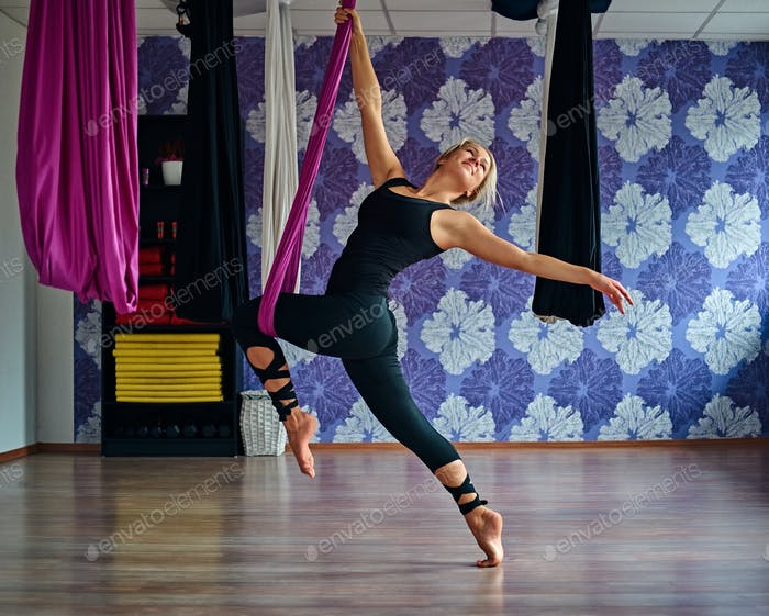 Young woman doing aerial yoga practice in purple hammock in fitness club.